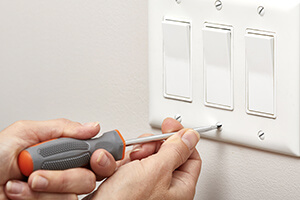 An electrician installing light switches in a home.